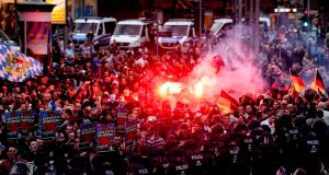 Right wing protesters light flares while facing police as they gather at the place where a man was stabbed in the night of in Chemnitz, Germany. PHotograph: Filip Singer/EPA