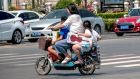 A woman rides her scooter with two children in Huaxian county in China's central Henan province. China appears set to end its two-child policy. Photograph:  AFP/Getty Images
