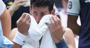 Novak Djokovic  takes a break from the heat while playing against Marton Fucsovics of Hungary during their Day 2 match in New York. Photograph: Timothy A. Clary/AFP/Getty Images