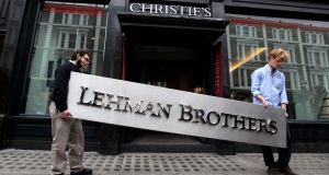 Two employees of Christie's manoeuvre the Lehman Brothers corporate logo as it went on auction in September 2010 in London. Photograph: Oli Scarff/Getty Images