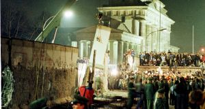 A big section of the Berlin Wall is lifted by a crane, February 20th, 1990. Photograph: Michael Probst/Reuters