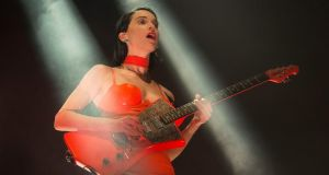 St Vincent: imperious in orange PVC, Annie Clark manipulates a selection of primary-colour guitars with demonic zest. Photograph: Dave Meehan