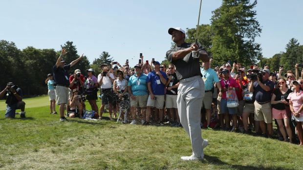 Woods plays his approach to the second. Photo: Patrick Smith/Getty Images