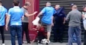 A still from a video posted on social media which appears to show a man wearing a Dublin GAA jersey (centre) kick  another man (red top, sitting) in the head.
