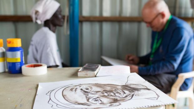 Irish artist Brian Maguire sketches Veronika Meer in the PoC capmp in Bentiu, South Sudan. Veronika fled here with her kids when conflict broke out in her town and her husband was killed. Photograph: Steve De Neef/Concern Worldwide