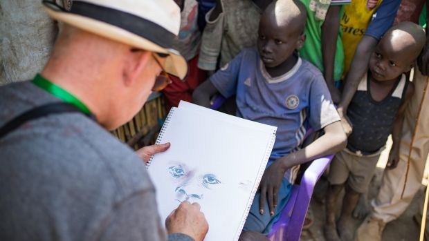 Brian Maguire sketches a young boy in the PoC camp in Bentiu, South Sudan. Photograph: Steve De Neef/Concern Worldwide.