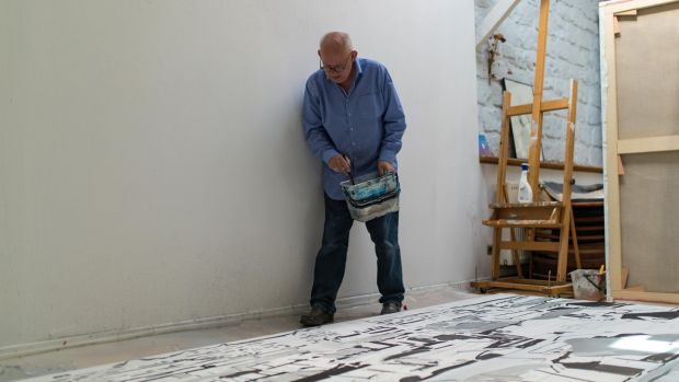 Brian Maguire working on his Sudan paintings in his studio