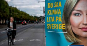 A woman rides her bike next to an election poster of Ebba Busch Thor, leader of the Christian Democrats Party  in Stockholm. The general election in Sweden takes place on Sunday. Photograph: Jonathan Nackstrand/AFP/Getty Images