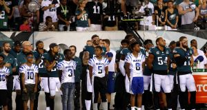 Members of the Philadelphia Eagles stand for the national anthem before they're NFL meeting with Atlanta Falcons. Photo: Mike Segar/Reuters
