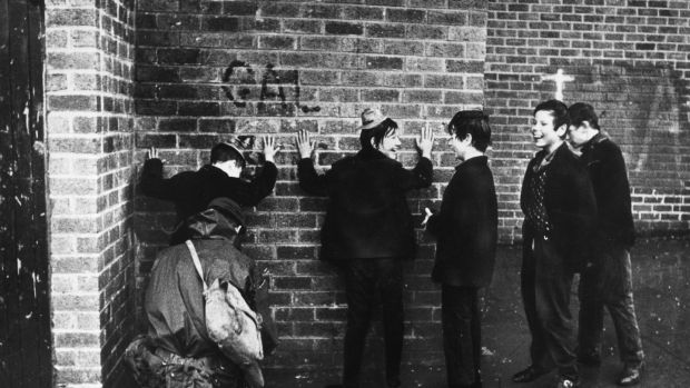 Schoolboys giggling while a soldier searches them in a street in the Ardoyne area of Belfast in 1971. Photograph: Keystone/ Getty Images )