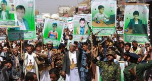 Supporters of Yemen's Houthi rebels raise Kalashnikovs and signs depicting children killed in a Saudi-led coalition air strike on a bus in August, at a rally in Saada. Photograph: Stringer/AFP/Getty