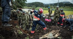 Soldiers and rescue workers search through mud covering a building destroyed by a landslide in Atsuma near Sapporo, Japan. Photograph:  Carl Court/Getty