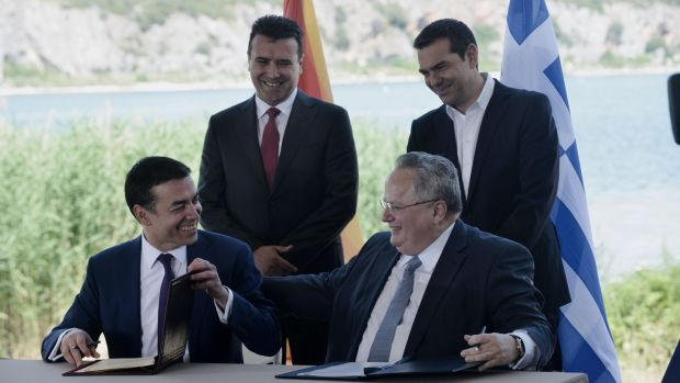 Greek foreign minister Nikos Kotzias (down, R) and his Macedonian counterpart Nikola Dimitrov (down, L) sign a preliminary accord as Greek prime minister Alexis Tsipras (R) and Macedonian prime minister Zoran Zaev stand behind, on the shore of the Lake Prespa. Photograph: Sakis Mitrolidis/AFP/Getty Images