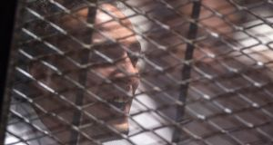 Egyptian photojournalist Mahmoud Abu Zeid, better known as Shawkan, reacts behind a grill after a verdict sentenced him to five years in Cairo, Egypt. Photograph: Mohamed Hossam/EPA