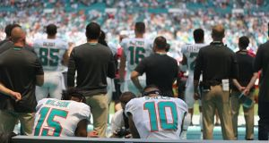 Kenny Stills and Albert Wilson of the Miami Dolphins sit on the bench during the playing of the national anthem. Photograph: Getty Images