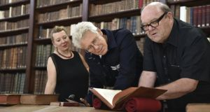 Adam Clayton of U2 and the band's former manager, Paul McGuinness look at an English-Irish dictionary dating from 1768 as Irish College director Nora Hickey M'sichili looks on.