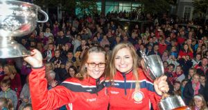 Senior camogie captain Aoife Murray and Intermediate captain Sarah Harrington hold aloft their All Ireland Trophies on arrival at the South Mall in Cork city. Photograph: Michael MacSweeeney/Provision