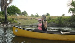 "Take your child to work day: ""Teaching my daughter how to spot wildlife along the river, although she wasn't nearly as interested by the Giant river otter as I was!"" Dr Anouska Kinahan with Luna in Guyana"