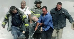 Rescue workers carry fatally injured New York City Fire Department chaplain, Fr Mychal Judge, from the wreckage of the World Trade Center in New York City on September 11th, 2001. Judge was the first official victim of the 9/11 attacks. Photograph: Shannon Stapleton/Reuters