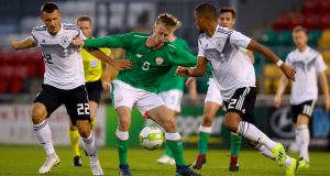 Henry Charsley is tackled by Maximilian Eggestein of Germany during the  Under-21 European Championship qualifier at  Tallaght Stadium. Photograph: Oisín Keniry/Inpho