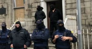 Gardaí and other masked men at the scene during an operation at 34 North Frederick Street in Dublin. Photograph: Jack Power