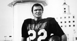 American actor Burt Reynolds holds a helmet while standing in a 'Mean Machine' football jersey in a still from the film, The Longest Yard, directed by Robert Aldrich, 1974. Photo: Paramount Pictures/Courtesy of Getty Images