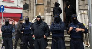While several men in balaclavas stood at the entrance to the property, more than a dozen gardaí wearing face masks blocked protesters from accessing the building. Photograph: Jack Power