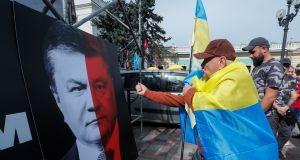 A protester   gestures at a placard with combo portrait picturing faces of the President Poroshenko and former president Yanukovich with a slogan 'No to elections with Yanukovich law' during their rally near the Parliament building in Kiev, Ukraine. Photograph: EPA