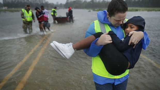 Volunteers help rescue three children from their flooded home in James City, US. Photograph: Chip Somodevilla/Getty Images