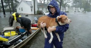 Volunteers help rescue residents and their pets from their flooded homes. Photograph: Chip Somodevilla/Getty Images