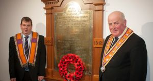 Deputy master of Loyal Orange Lodge 1063, Stewart McClean, and grand master of the Grand Orange Lodge of Ireland Edward Stevenson (right), with the restored first World War memorial tablet after it was destroyed in an arson attack in 2014 in Newtowncunningham Orange Hall. Photograph: Orange Order/PA Wire