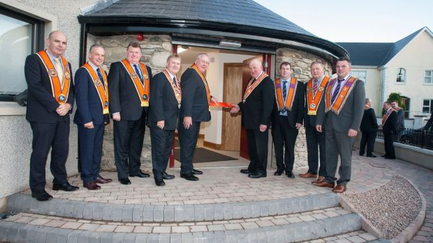 Grand master of the Grand Orange Lodge of Ireland Edward Stevenson cuts the ribbon at the official opening of the restored Newtowncunningham Orange Hall, as senior Orange Order members watch. Photograph: Orange Order/PA Wire