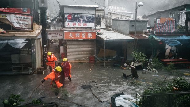 Firefighters escort people through floodwaters in Hong Kong, China. Photograph: Anthony Kwan/Bloomberg