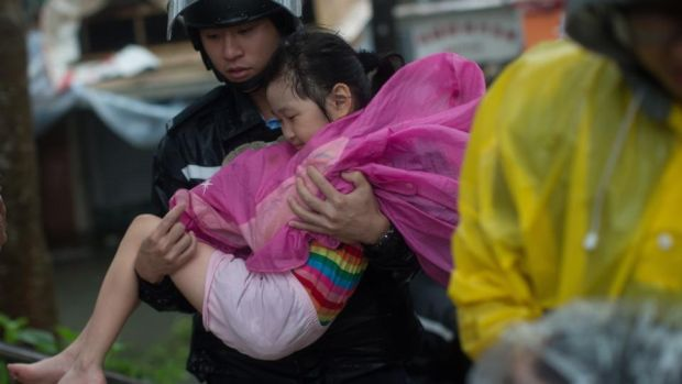 A police officer carries young girl to safety during Typhoon Mangkhut in Lei Yu Mun, Hong Kong. Photograph: Jerome Favre/EPA