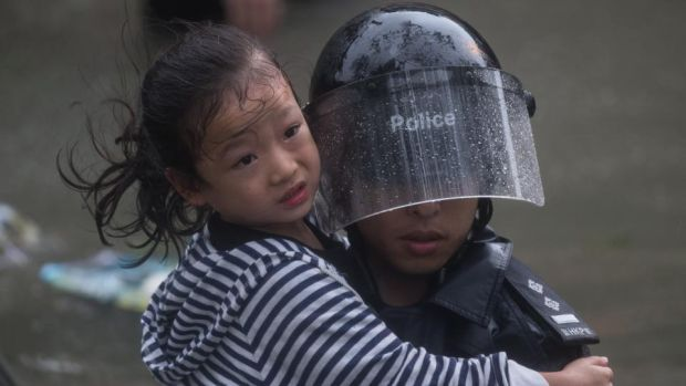 A police officer rescues a child from a flooded street during Typhoon Mangkhut in Lei Yu Mun, Hong Kong. Photograph: Jerome Favre/EPA