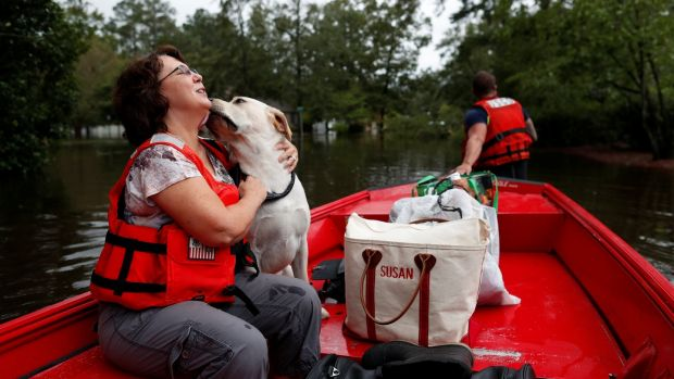 Susan Hedgpeth hugs her dog Cooper, as they go to higher ground via the United States Coast Guard during Tropical Storm Florence in Lumberton, North Carolina. Photograph: Randall Hill/Reuters.