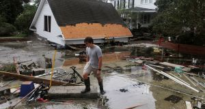 Resident Joseph Eudi looks at flood debris and storm damage from Tropical Storm Florence at a home on East Front Street in New Bern, North Carolina. Photograph: Gray Whitley/Sun Journal via AP.