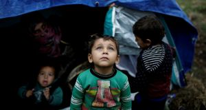 A Syrian refugee boy stands in front of his family tent at a makeshift camp for refugees and migrants next to the Moria camp on  Lesbos. Photograph: Alkis Konstantinidis/Reuters