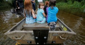 Iva Williamson peers behind her as she joins neighbors and pets in fleeing rising flood waters in the aftermath of Hurricane Florence in Leland, North Carolina, September 16, 2018. Photograph: Reuters