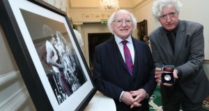 The President receives a commemorative silver Rory Gallagher coin commissioned by the Central Bank, above, with Rory Gallagher's brother Dónal. Photograph: Maxwell's