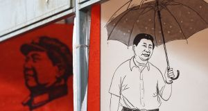 Posters of late communist leader Mao Zedong and President Xi Jinping  at a market in Beijing:  next step is to bring the China Dream overseas. Photograph: Greg Baker/AFP/Getty