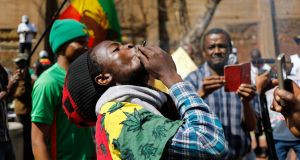 A Rastafarian and supporter of the legislation of marijuana light a joint in Johannesburg, as they celebrate after the Constitutional Court ruled that the personal use and growing of marijuana in South Africa is legal. Photograph: Kim Ludbrook/EPA