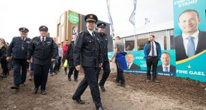 Garda Commissioner Drew Harris passes a poster of Taoiseach Leo Varadkar at National Ploughing Championships in Tullamore: the Government must find the political vision and resolve to use the commission's report as a platform for change. Photograph: Tom Honan