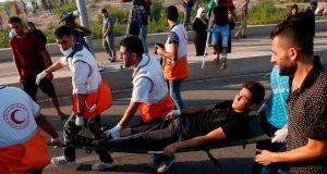 Medics help evacuate a wounded Palestinian protestor during a demonstration at the Erez crossing with Israel on Tuesday, in the northern Gaza Strip. Photograph: Said Khatib/AFP/Getty Images