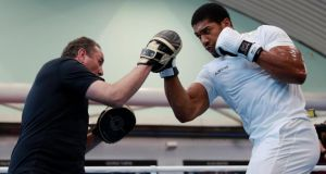 Anthony Joshua on the pads with trainer Robert McCracken ahead of his heavyweight clash with Alexander Povetkin. Photograph: Andrew Coulridge/Reuters