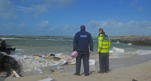 Gardaí from Clifden Garda station survey the wreckage from the caravan that was washed into the sea at Claddaghduff. Photograph: Conor Mc Keown