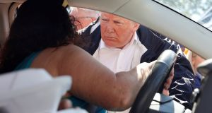 US president Donald Trump talks with a driver after handing out food  during a tour of Hurricane Florence recovery efforts in New Bern, North Carolina, US. Photograph: Kevin Lamarque/Reuters