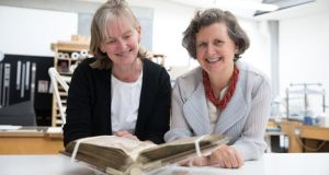 Trinity College Dublin librarian and college archivist Helen Shenton with Prof Rachel Moss, head of history of art and architecture at Trinity, with the Book of Durrow. Photograph: Trinity College Dublin