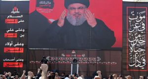 "Hizbullah leader Sayyed Hassan Nasrallah addresses  supporters on a screen in Beirut, Lebanon. Hizbullah will maintain a presence in Syria ""until further notice"". Photograph: Aziz Taher/Reuters"