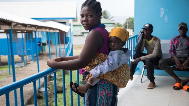 A woman and baby wait next to a tuberculosis ward at the TB Annex Hospital in Monrovia. Photograph: Sally Hayden